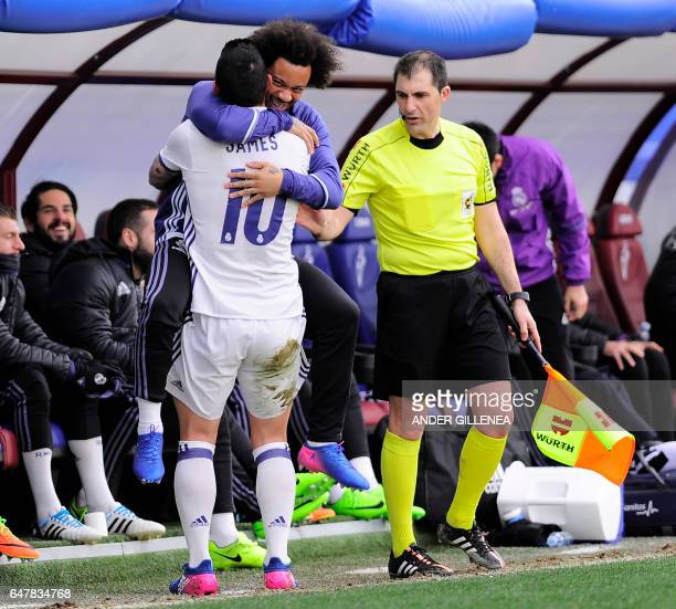 Real Madrid's Colombian midfielder James Rodriguez celebrates with teammate Brazilian defender Marcelo after scoring their team's third goal during...