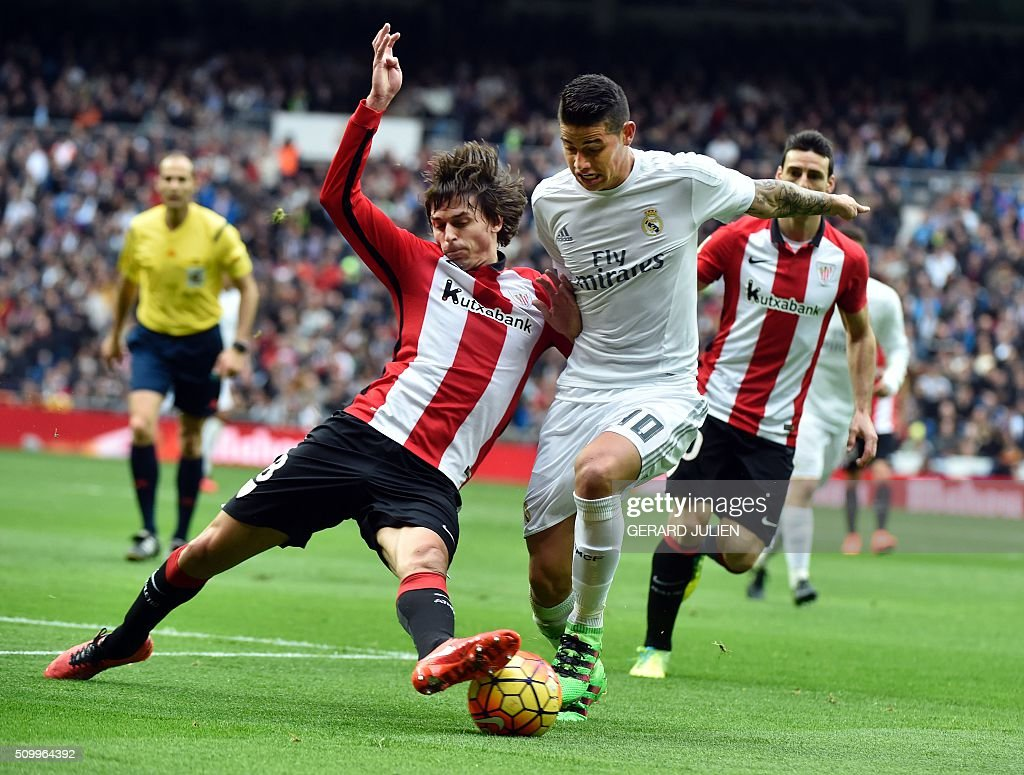 Real Madrid's Colombian midfielder James Rodriguez (L) vies with Athletic Bilbao's midfielder Ander Iturraspe during the Spanish league football match Real Madrid CF vs Athletic Club Bilbao at the Santiago Bernabeu stadium in Madrid on February 13, 2016. / AFP / GERARD JULIEN