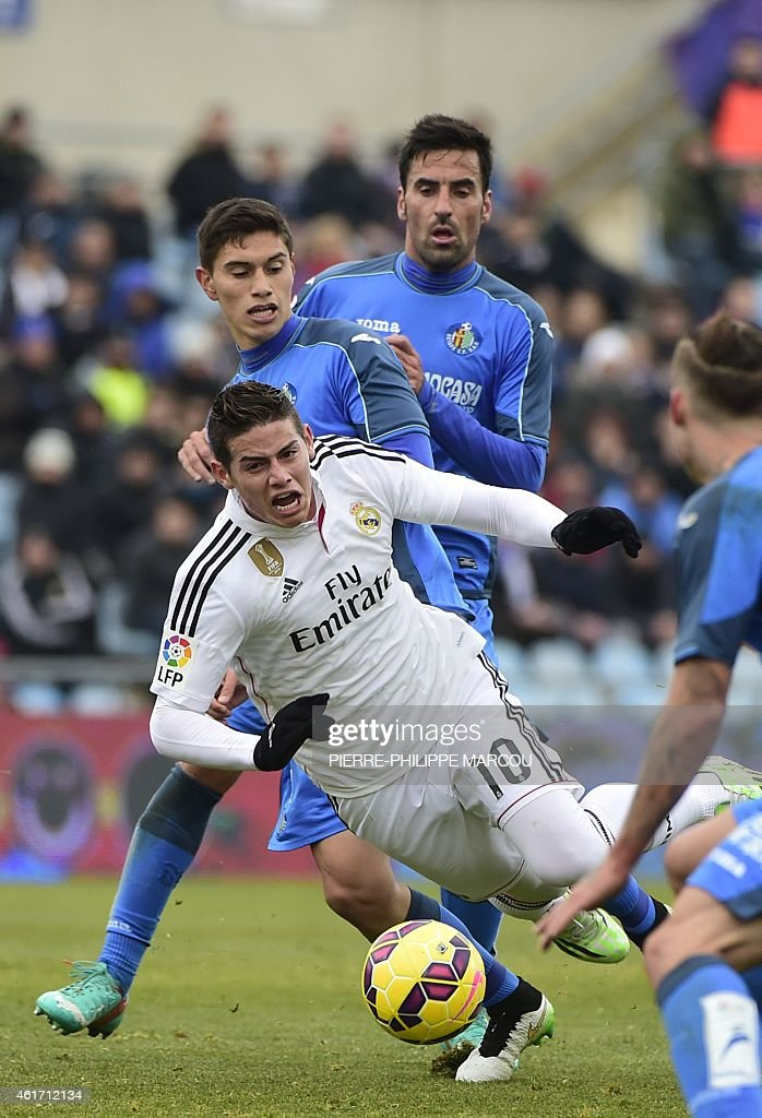 Real Madrid's Colombian midfielder <a gi-track='captionPersonalityLinkClicked' href=/galleries/search?phrase=James+Rodriguez&family=editorial&specificpeople=4422074 ng-click='$event.stopPropagation()'>James Rodriguez</a> (L) vies wth Getafe's Uruguayan defender Emiliano Velazquez (C) and Getafe's midfielder Juan Rodriguez (R) during the Spanish league football match Getafe CF vs Real Madrid CF at the Coliseum Alfonso Perez stadium in Getafe on January 18, 2015. AFP PHOTO/ PIERRE-PHILIPPE MARCOU