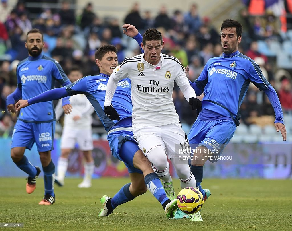 Real Madrid's Colombian midfielder <a gi-track='captionPersonalityLinkClicked' href=/galleries/search?phrase=James+Rodriguez&family=editorial&specificpeople=4422074 ng-click='$event.stopPropagation()'>James Rodriguez</a> (C) vies wth Getafe's Uruguayan defender Emiliano Velazquez (L) and Getafe's midfielder Juan Rodriguez (R) during the Spanish league football match Getafe CF vs Real Madrid CF at the Coliseum Alfonso Perez stadium in Getafe on January 18, 2015.