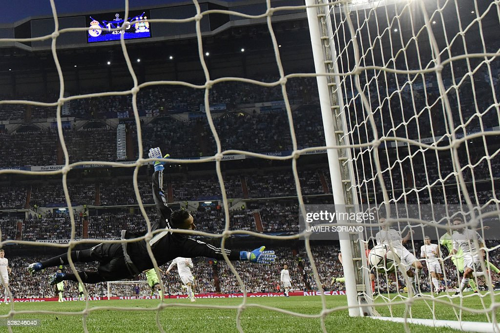 Real Madrid's Costa Rican goalkeeper Keylor Navas dives for a ball during the UEFA Champions League semi-final second leg football match Real Madrid CF vs Manchester City FC at the Santiago Bernabeu stadium in Madrid on May 4, 2016. / AFP / JAVIER