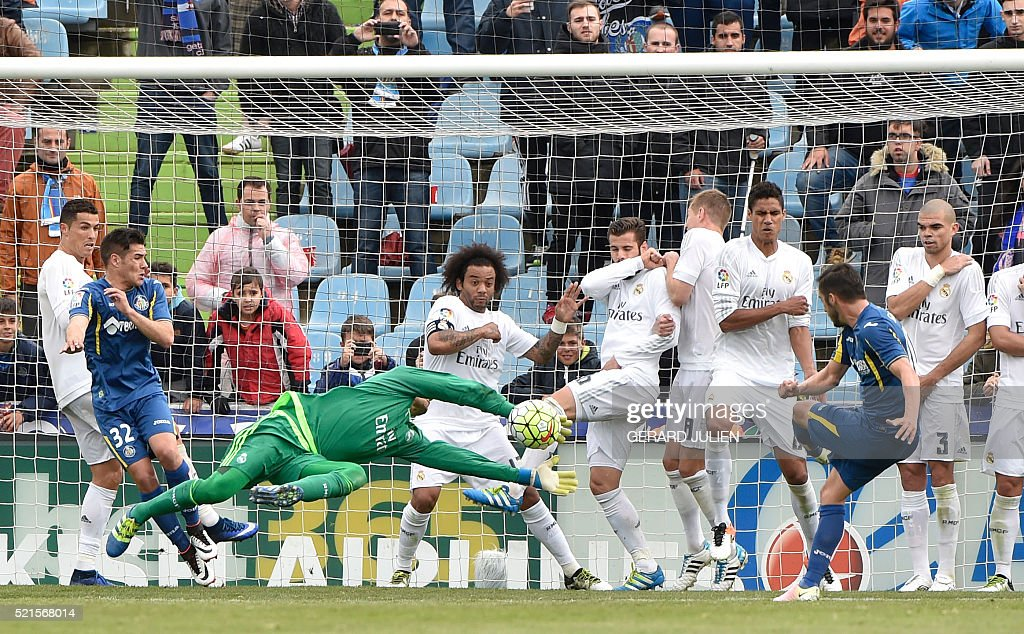 Real Madrid's Costa Rican goalkeeper Keylor Navas dives for the ball during the Spanish league football match Getafe CF vs Real Madrid CF at the...