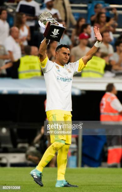Real Madrid's Costa Rican goalkeeper Keylor Navas holds up the trophy as he celebrates their Supercup after winning the second leg of the Spanish...