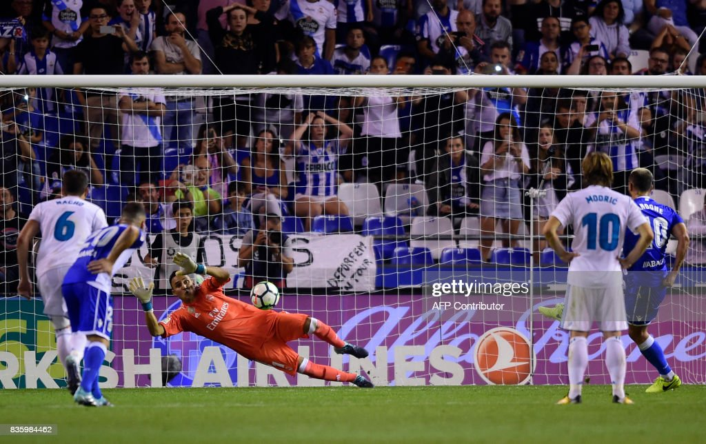 TOPSHOT - Real Madrid's Costa Rican goalkeeper Keylor Navas stops a penalty shot by Deportivo La Coruna's Romanian forward Florin Andone (R) during the Spanish league footbal match RC Deportivo de la Coruna vs Real Madrid CF at the Municipal de Riazor stadium in La Coruna on August 20, 2017. /