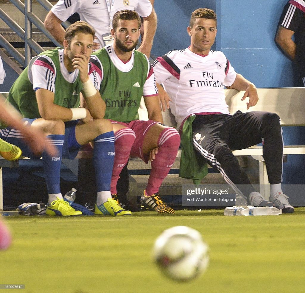 Real Madrid's Cristiano Ronaldo, right, watches from the bench as his team plays AS Roma in the Guinness International Champions Cup at the Cotton Bowl in Dallas on Tuesday, July 29, 2014.