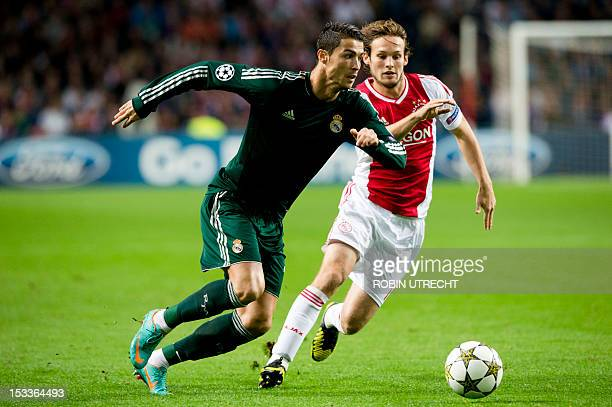 Real Madrid's Cristiano Ronaldo runs past Ajax Amsterdam's Daley Blind during the UEFA Champions League Group D football match Ajax Amsterdam vs Real...