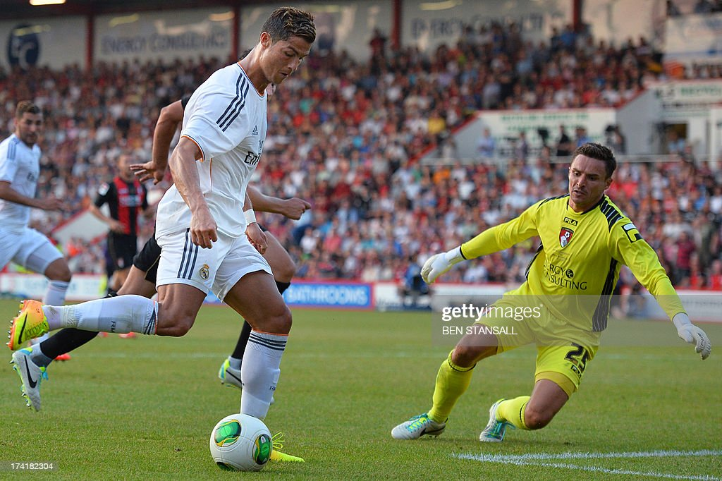 Real Madrid's Cristiano Ronaldo (L) scores his second goal past Bournemouth's goalkeeper Darryl Flahavan during the pre-season friendly football match between Bournemouth and Real Madrid at the Goldsands Stadium in Bournemouth , England on July 21, 2013. AFP PHOTO/BEN STANSALL