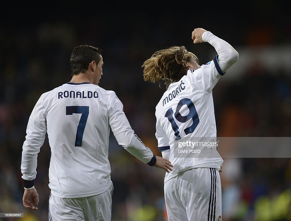Real Madrid's Croatian midfielder Luka Modric (R) celebrates with Real Madrid's Portuguese forward Cristiano Ronaldo (L) after scoring during the Spanish League football match Real Madrid CF vs RCD Mallorca at the Santiago Bernabeu stadium in Madrid on March 16, 2013. AFP PHOTO/ DANI POZO