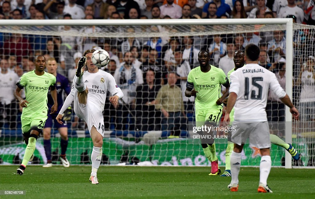 Real Madrid's Croatian midfielder Luka Modric (2nd L) controls the ball behind Manchester City's Brazilian midfielder Fernandinho (L) and Manchester City's Ivorian midfielder and captain Yaya Toure during the UEFA Champions League semi-final second leg football match Real Madrid CF vs Manchester City FC at the Santiago Bernabeu stadium in Madrid, on May 4, 2016. / AFP / GERARD