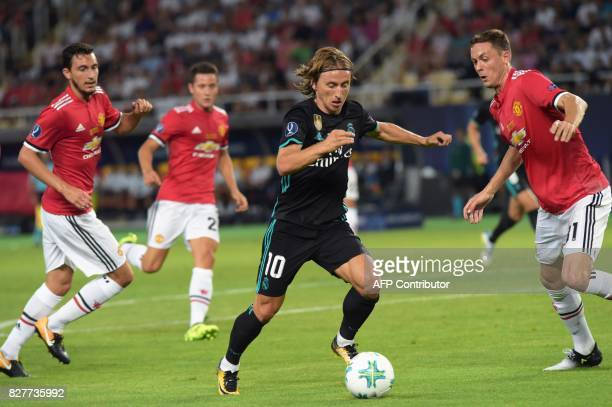 Real Madrid's Croatian midfielder Luka Modric drives the ball ahead of Manchester United's Serbian midfielder Nemanja Matic during the UEFA Super Cup...