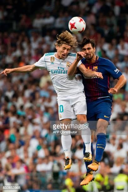 Real Madrid's Croatian midfielder Luka Modric heads the ball with Barcelona's midfielder Sergi Roberto during the second leg of the Spanish Supercup...