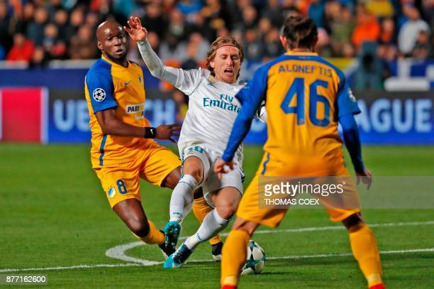 Real Madrid's Croatian midfielder Luka Modric is tackled Apoel's Beninese forward Mickael Pote and Apoel's Cypriot midfielder Efstathios Aloneftis...