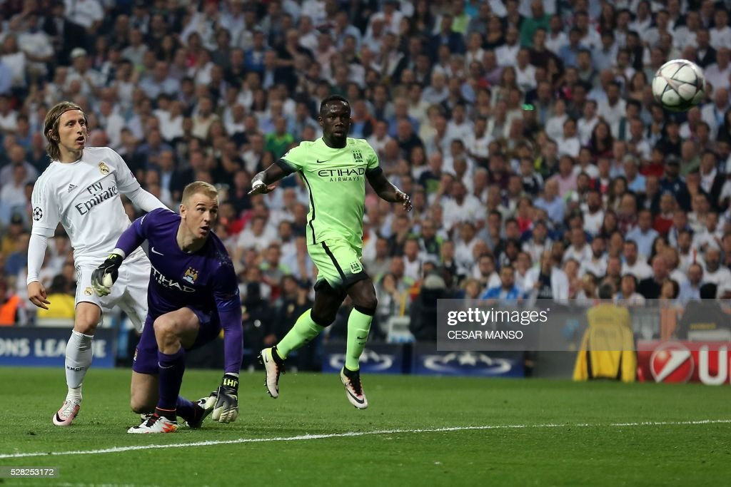 Real Madrid's Croatian midfielder Luka Modric (L), Manchester City's English goalkeeper Joe Hart (C) and Manchester City's Argentinian defender Nicolas Otamendi eye the ball during the UEFA Champions League semi-final second leg football match Real Madrid CF vs Manchester City FC at the Santiago Bernabeu stadium in Madrid, on May 4, 2016. / AFP / CESAR