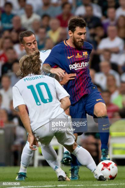 Real Madrid's Croatian midfielder Luka Modric vies with Barcelona's Argentinian forward Lionel Messi during the second leg of the Spanish Supercup...