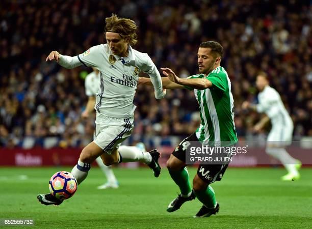 Real Madrid's Croatian midfielder Luka Modric vies with Betis' Danish defender Riza Durmisi during the Spanish league footbal match Real Madrid CF vs...