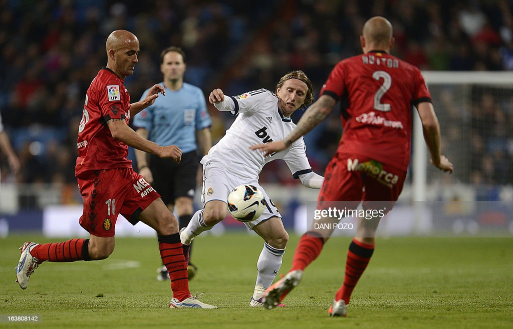 Real Madrid's Croatian midfielder Luka Modric (C) vies with Mallorca's Portuguese defender Jose Nunes (L) during the Spanish League football match Real Madrid CF vs RCD Mallorca at the Santiago Bernabeu stadium in Madrid on March 16, 2013. Real Madrid won 5-2.