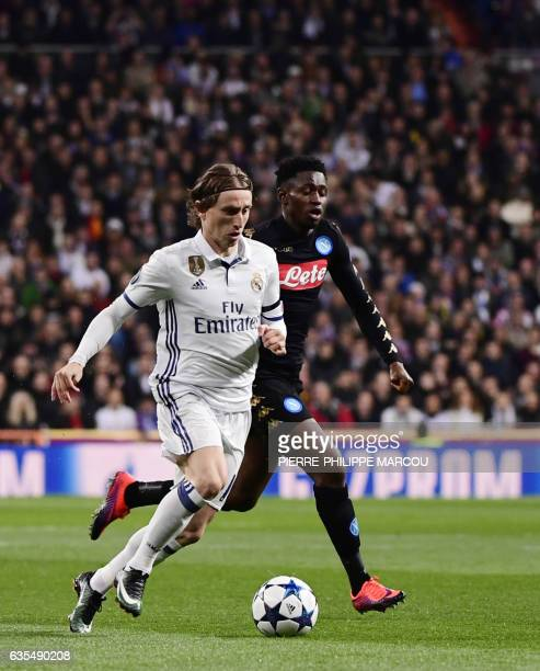 Real Madrid's Croatian midfielder Luka Modric vies with Napoli's midfielder from Guinea Amadou Diawara during the UEFA Champions League round of 16...