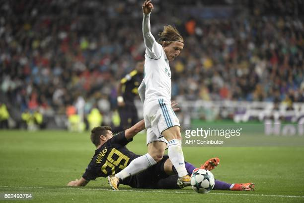 Real Madrid's Croatian midfielder Luka Modric vies with Tottenham Hotspur's English midfielder Harry Winks during the UEFA Champions League group H...