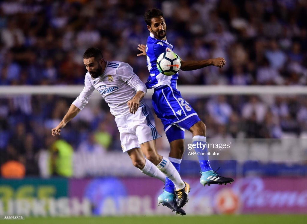 Real Madrid's defender Dani Carvajal (L) jumps for the ball with Deportivo La Coruna's Costa Rican midfielder Celso Borges during the Spanish league footbal match RC Deportivo de la Coruna vs Real Madrid CF at the Municipal de Riazor stadium in La Coruna on August 20, 2017. /