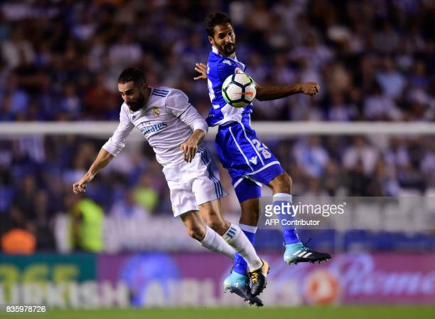 Real Madrid's defender Dani Carvajal jumps for the ball with Deportivo La Coruna's Costa Rican midfielder Celso Borges during the Spanish league...