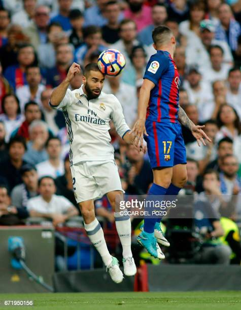 Real Madrid's defender Dani Carvajal jumps for the ball with Barcelona's forward Paco Alcacer during the Spanish league football match Real Madrid CF...