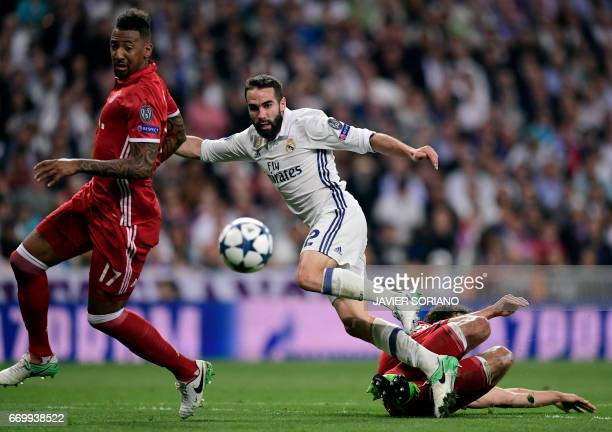 Real Madrid's defender Dani Carvajal vies with Bayern Munich's defender Mats Hummels and Bayern Munich's defender Jerome Boateng during the UEFA...