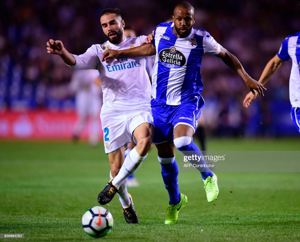 Real Madrid's defender Dani Carvajal (L) vies with Deportivo La Coruna's Brazilian defender Sidnei during the Spanish league footbal match RC Deportivo de la Coruna vs Real Madrid CF at the Municipal de Riazor stadium in La Coruna on August 20, 2017. /
