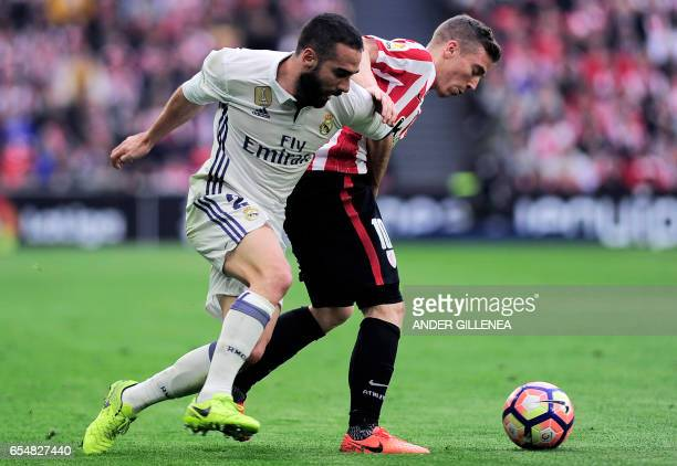 Real Madrid's defender Daniel Carvajal vies with Athletic Bilbao's forward Iker Muniain during the Spanish league football match Athletic Club Bilbao...