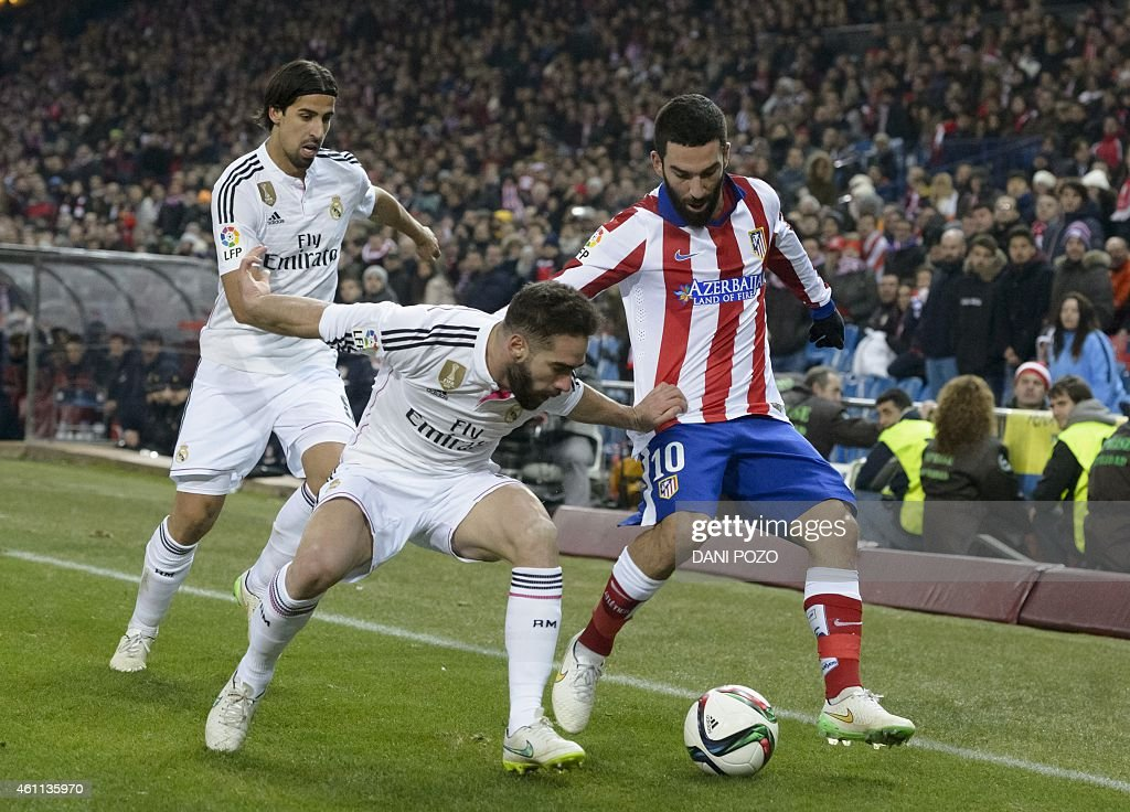 Real Madrid's defender Daniel Carvajal (L) vies with Atletico Madrid's Turkish midfielder <a gi-track='captionPersonalityLinkClicked' href=/galleries/search?phrase=Arda+Turan&family=editorial&specificpeople=2179402 ng-click='$event.stopPropagation()'>Arda Turan</a> during the Spanish Copa del Rey (King's Cup) round of 16 first leg football match Club Atletico de Madrid vs Real Madrid CF at the Vicente Calderon stadium in Madrid on January 7, 2015.