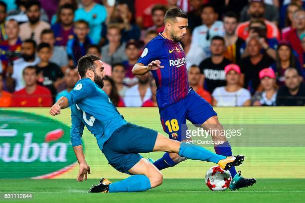 Real Madrid's defender Daniel Carvajal vies with Barcelona's defender Jordi Alba during the first leg of the Spanish Supercup football match between...