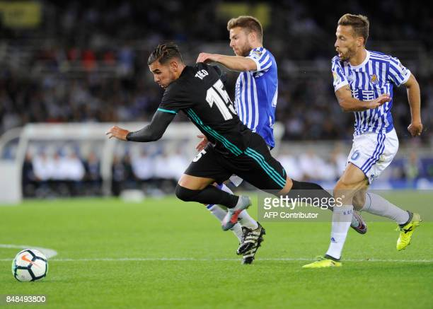 Real Madrid's defender from France Theo Hernandez vies with Real Sociedad's midfielder from Spain Asier Illarramendi and Real Sociedad's midfielder...