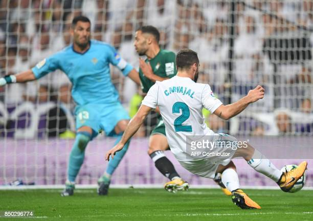 Real Madrid's defender from Spain Dani Carvajal shoots in front of Real Betis' goalkeeper from Spain Antonio Adan during the Spanish league football...