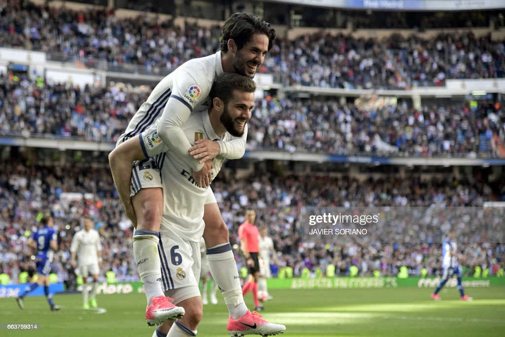 Real Madrid's defender Nacho Fernandez (down) celebrates a goal with Real Madrid's midfielder Isco during the Spanish league football match Real Madrid CF vs Deportivo Alaves at the Santiago Bernabeu stadium in Madrid on April 2, 2017. /