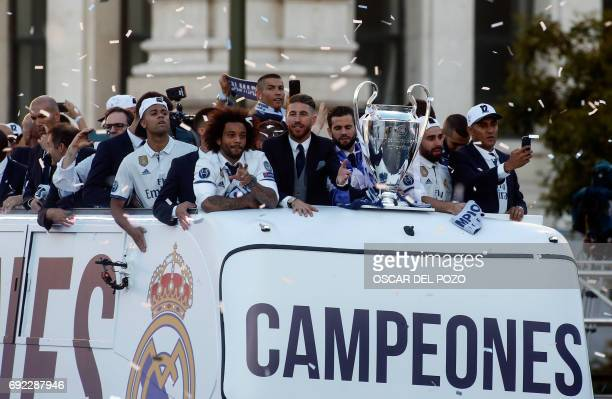 Real Madrid's defender Sergio Ramos and Real Madrid's Brazilian defender Marcelo stand at the front of the bus near the trophy as the team arrives to...