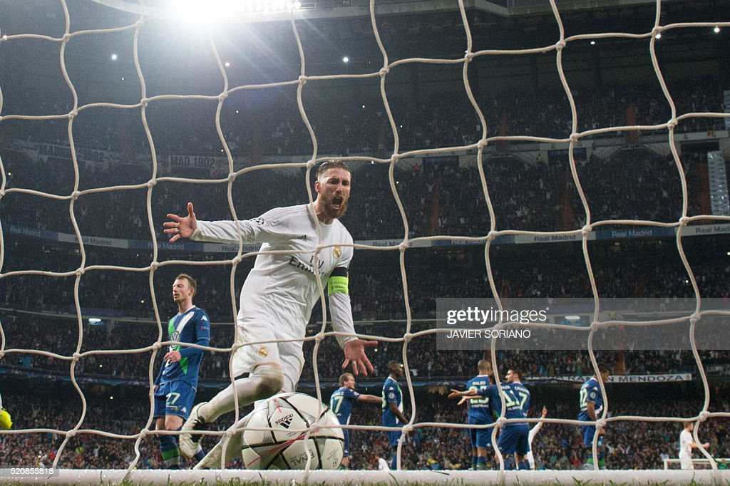 Real Madrid's defender Sergio Ramos celebrates after Real Madrid's Portuguese forward Cristiano Ronaldo scored his third goal during the Champions League quarter-final second leg football match Real Madrid vs Wolfsburg at Santiago Bernabeu stadium in Madrid on April 12, 2016. / AFP / JAVIER