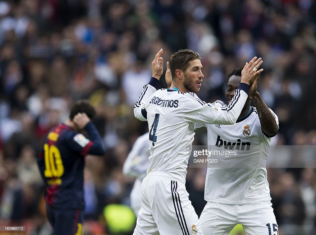 Real Madrid's defender Sergio Ramos (L) celebrates with Real Madrid's Ghanaian midfielder Michael Essien after scoring during the 'El clasico' Spanish League football match Real Madrid vs Barcelona at the Santiago Bernabeu stadium in Madrid on March 2, 2013. Real Madrid won 2-1.