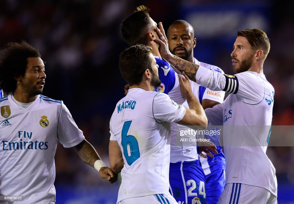 TOPSHOT - Real Madrid's defender Sergio Ramos (R) clashes with Deportivo La Coruna's Swiss defender Fabian Schar during the Spanish league footbal match RC Deportivo de la Coruna vs Real Madrid CF at the Municipal de Riazor stadium in La Coruna on August 20, 2017. /