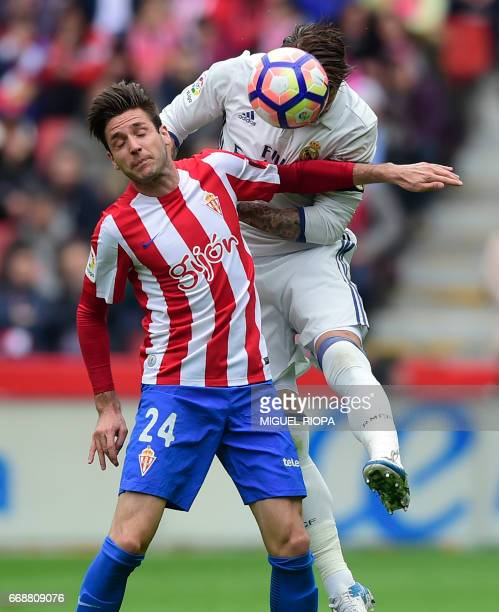 Real Madrid's defender Sergio Ramos heads the ball with Sporting Gijon's Croatian forward Duje Cop during the Spanish league football match Real...