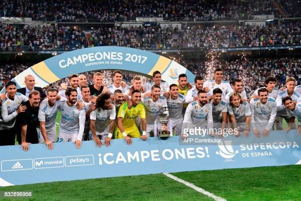 TOPSHOT Real Madrid's defender Sergio Ramos holds the trophy as he and teammates celebrate their Supercup after winning the second leg of the Spanish...