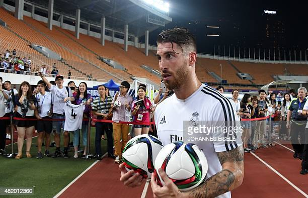 Real Madrid's defender Sergio Ramos holds two ball after a training session on the eve of the International Champions Cup football match between...