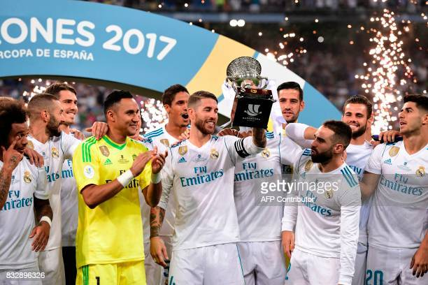 Real Madrid's defender Sergio Ramos holds up the trophy as he and teammates celebrate their Supercup after winning the second leg of the Spanish...