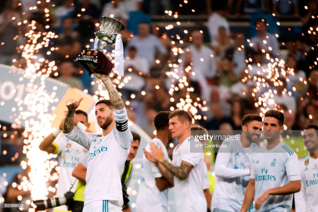 TOPSHOT - Real Madrid's defender Sergio Ramos (L) holds up the trophy as he celebrates their Supercup after winning the second leg of the Spanish Supercup football match Real Madrid vs FC Barcelona at the Santiago Bernabeu stadium in Madrid, on August 16, 2017. /