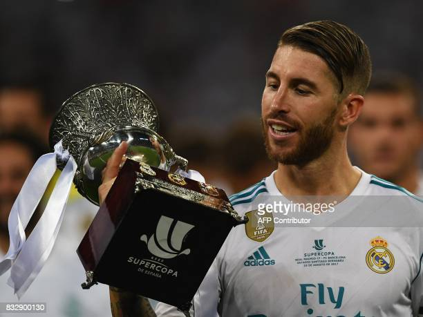 Real Madrid's defender Sergio Ramos holds up the trophy as he celebrates their Supercup after winning the second leg of the Spanish Supercup football...