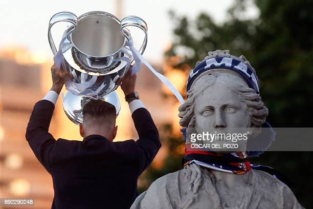 Real Madrid's defender Sergio Ramos holds up the trophy to celebrate the team's win on Plaza Cibeles in Madrid on June 4 2017 after the UEFA...