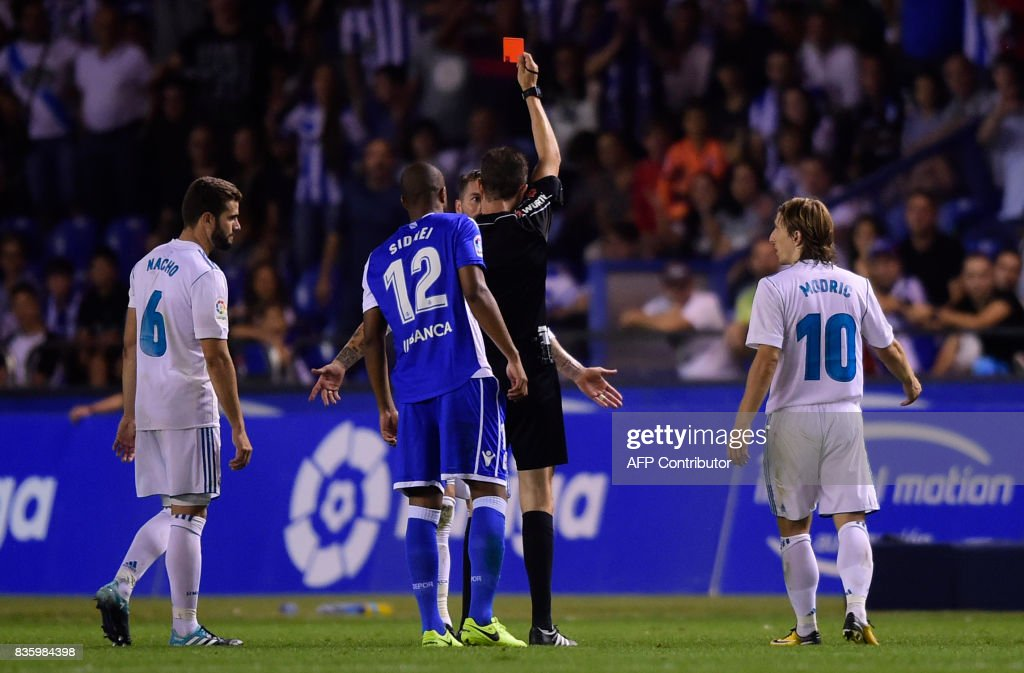 TOPSHOT - Real Madrid's defender Sergio Ramos is shown a red card by the referee during the Spanish league footbal match RC Deportivo de la Coruna vs Real Madrid CF at the Municipal de Riazor stadium in La Coruna on August 20, 2017. Real Madrid won 3-0. /