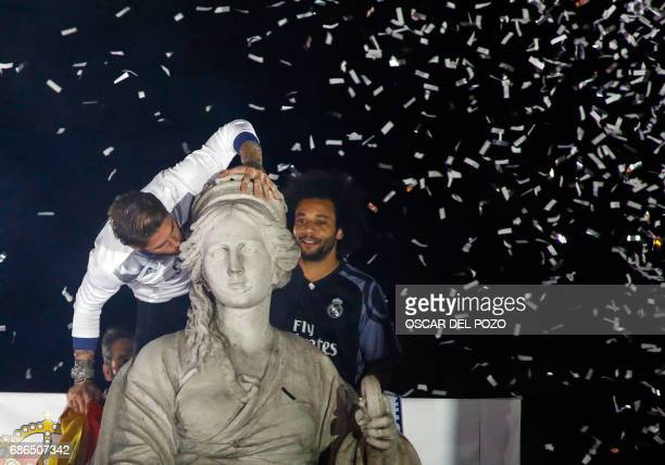 TOPSHOT Real Madrid's defender Sergio Ramos kisses the statue of goddess Cybele beside Real Madrid's Brazilian defender Marcelo as they celebrate the...