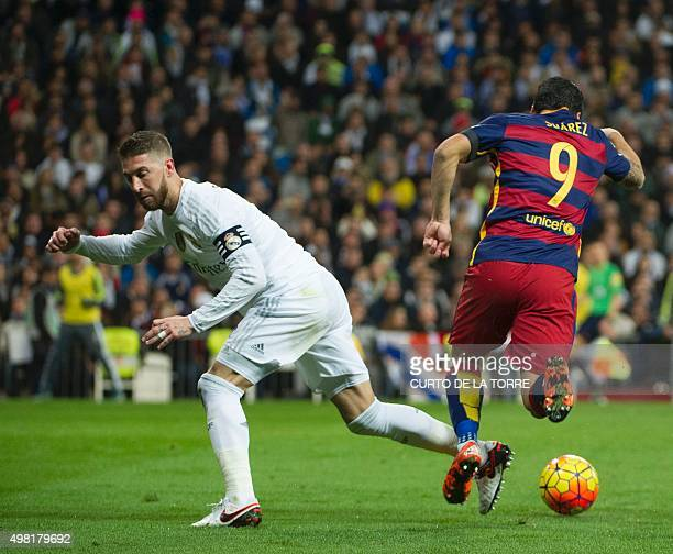 Real Madrid's defender Sergio Ramos vies with Barcelona's Uruguayan forward Luis Suarez during the Spanish league 'Clasico' football match Real...