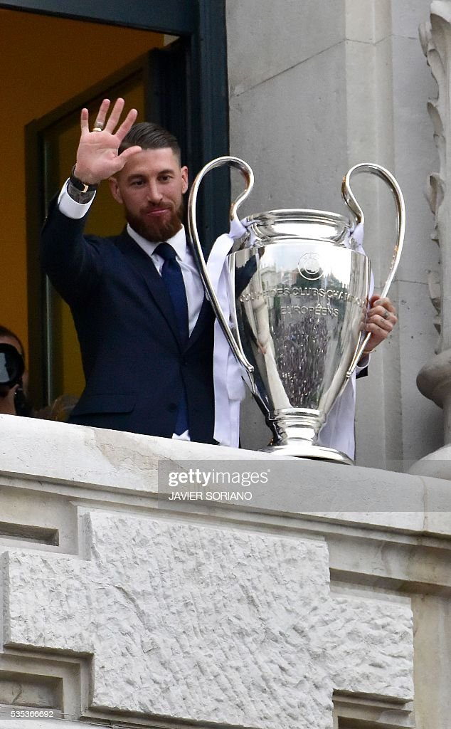 Real Madrid's defender Sergio Ramos waves as he shows the trophy from Madrid town hall's balcony on May 29, 2016 the day after winning the UEFA Champions League final foobtall match against Club Atletico de Madrid, held in Milan, Italy on May 28, 2016. / AFP / JAVIER
