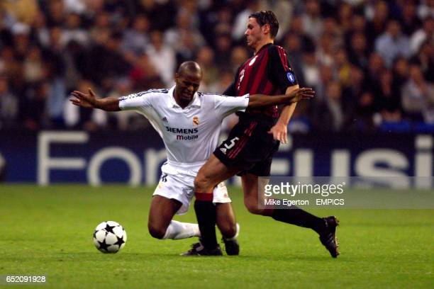 Real Madrid's Flavio Conceicao goes down under the challenge of AC Milan's Fernando Redondo