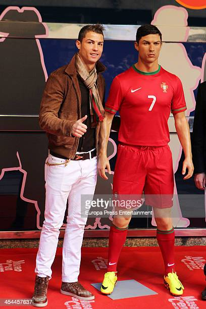 Real Madrid's football player Cristiano Ronaldo poses near his wax figure during its presentation on December 7 2013 in Madrid Spain